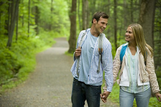 Close-up of a young couple walking and holding hands : Stock Photo