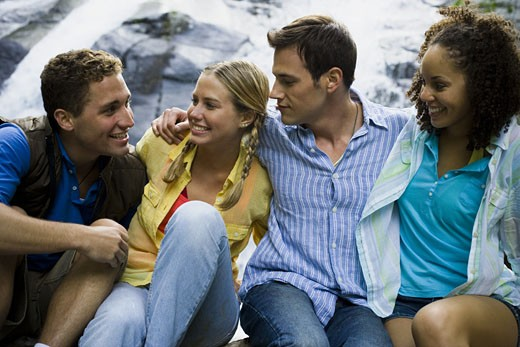 Close-up of two young women and two young men smiling : Stock Photo