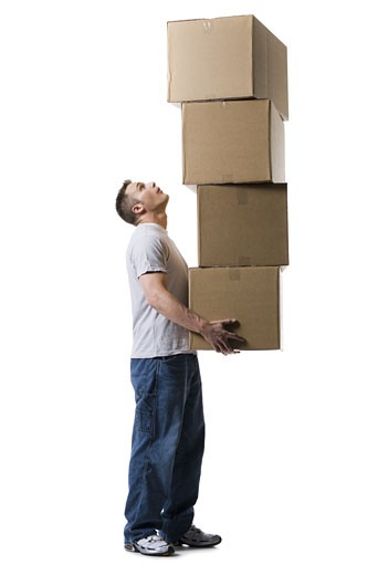 Profile of a young man holding a stack of cardboard boxes : Stock Photo