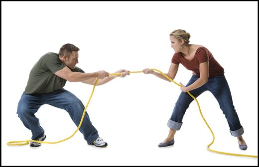 Stock Photo: 1660R-28466 Young couple playing tug-of-war