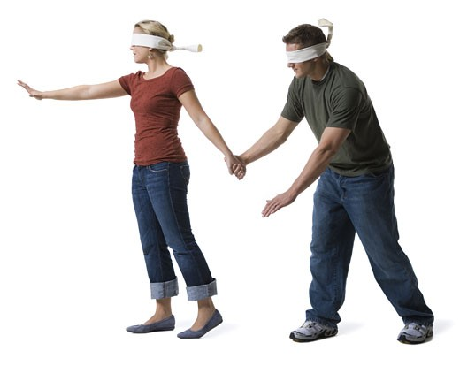 Blindfolded young woman leading to a blindfolded young man : Stock Photo