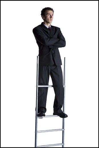 Businessman standing on corporate ladder : Stock Photo