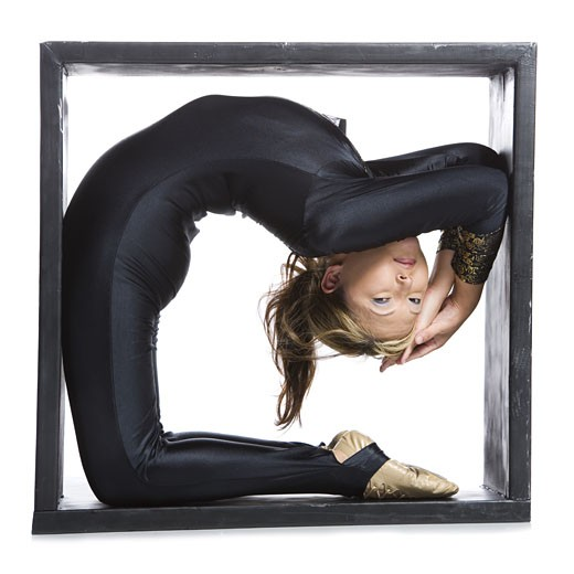 Female contortionist inside the box : Stock Photo
