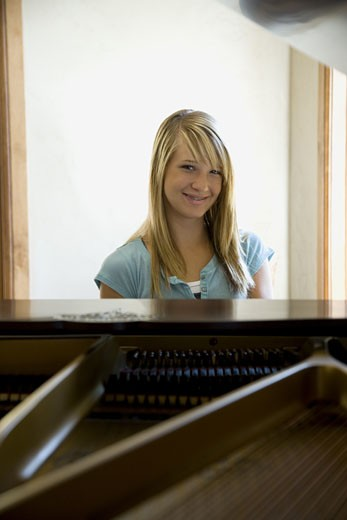 Young woman playing piano : Stock Photo
