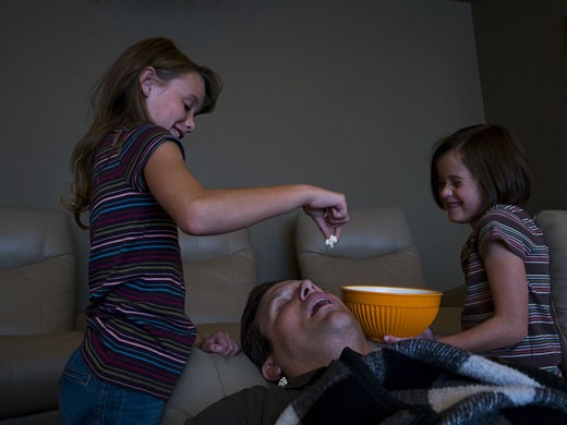 Daughters dropping popcorn into sleeping father's mouth : Stock Photo