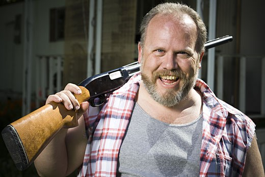 Overweight man with a shotgun : Stock Photo