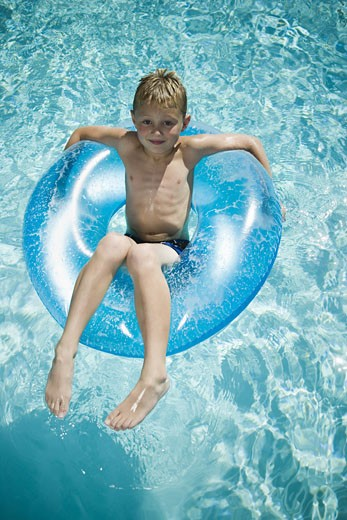 Stock Photo: 1660R-29797 Young boy floating on life ring in swimming pool