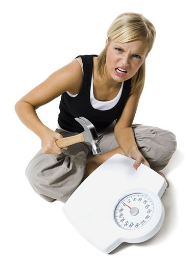 Frustrated dieting woman smashing bathroom scale with a hammer : Stock Photo