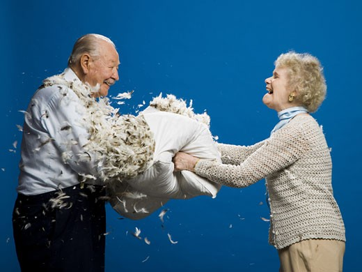 Older couple pillow fighting : Stock Photo
