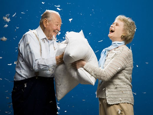 Stock Photo: 1660R-30100 Older couple pillow fighting