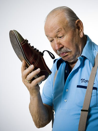 Stock Photo: 1660R-30122 Male bowler sniffing stinky bowling shoes