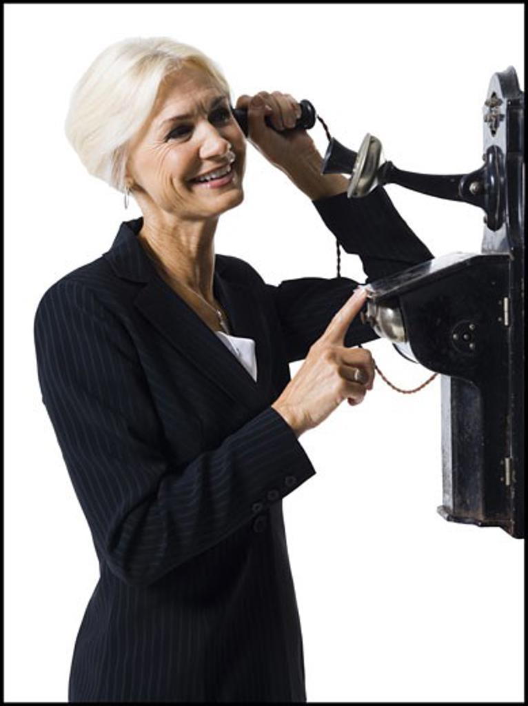 Stock Photo: 1660R-30173 Businesswoman speaking on antique telephone