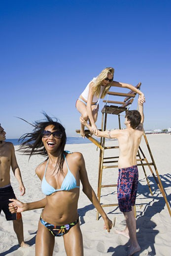 Stock Photo: 1660R-3019 Four young people on the beach