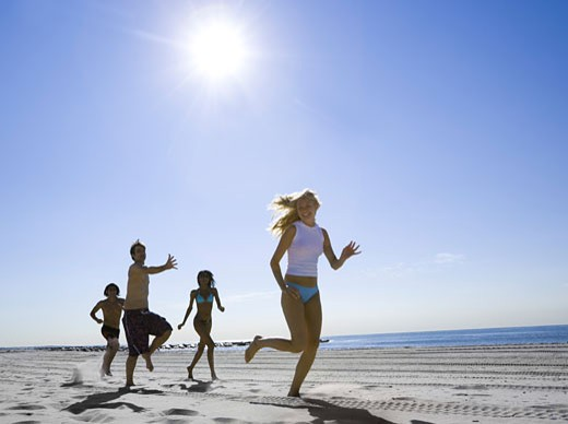 Low angle view of four young people running on the beach : Stock Photo