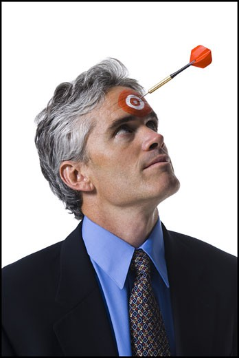 Stock Photo: 1660R-30260 Man with bull's-eye on forehead and dart coming toward him