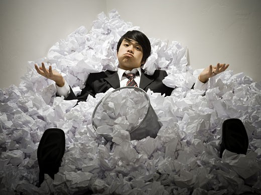 Stock Photo: 1660R-30517 Businessman buried in mountain of crumpled papers
