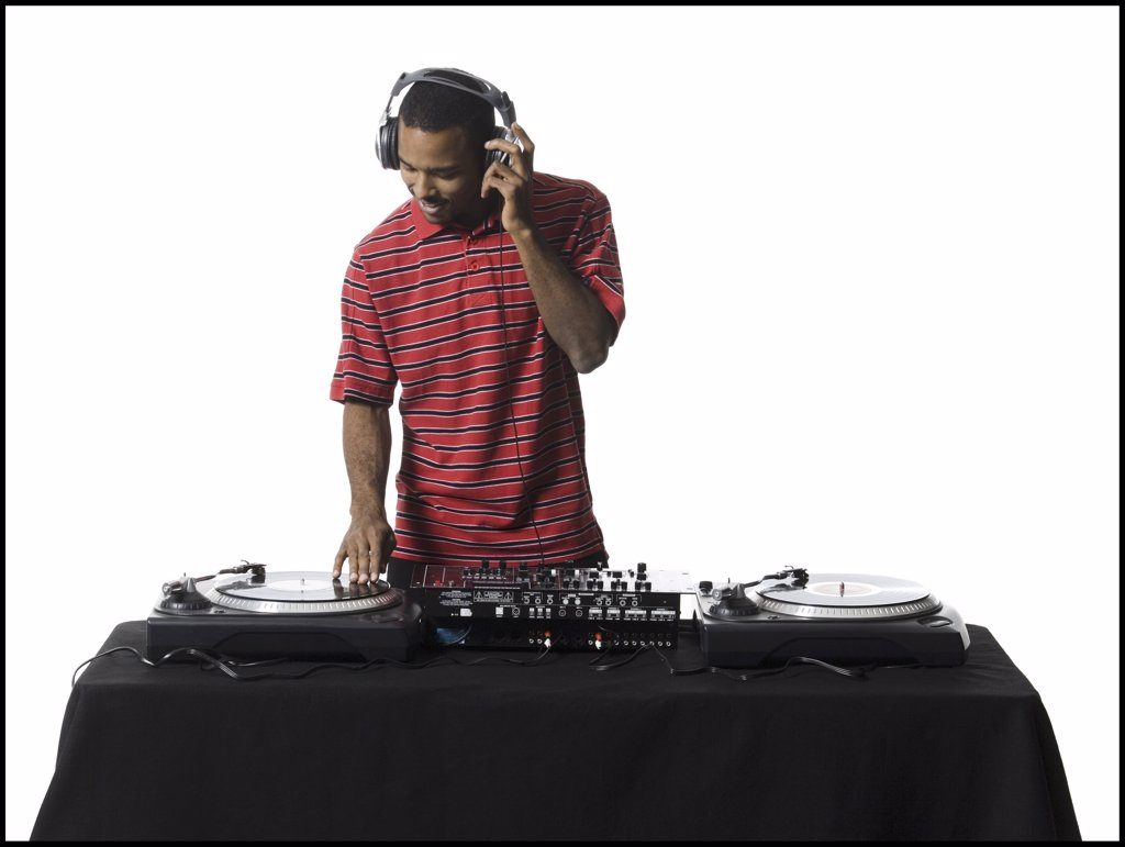 DJ with headphones spinning records : Stock Photo
