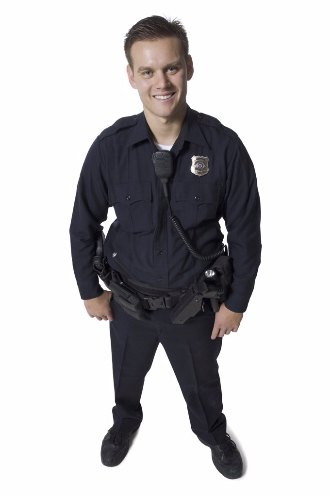 Male police officer standing with arms crossed smiling : Stock Photo