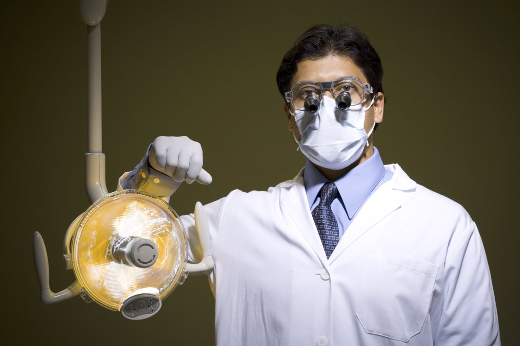 Stock Photo: 1660R-31618 Male doctor or dentist with surgical lamp smiling