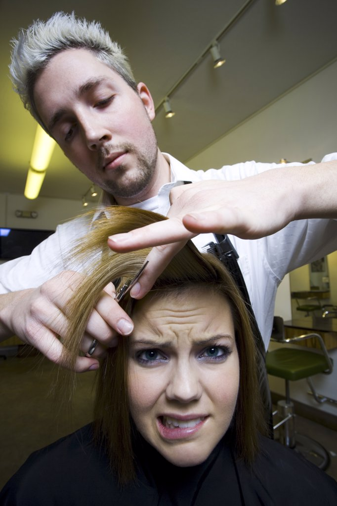 Stock Photo: 1660R-31620 Woman having hair cut by hairdresser