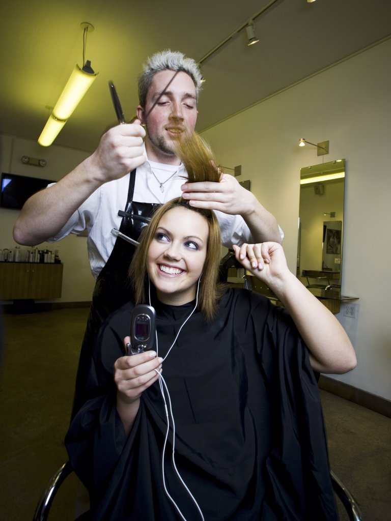 Stock Photo: 1660R-31629 Young woman listening to music on cell phone at hairdresser's