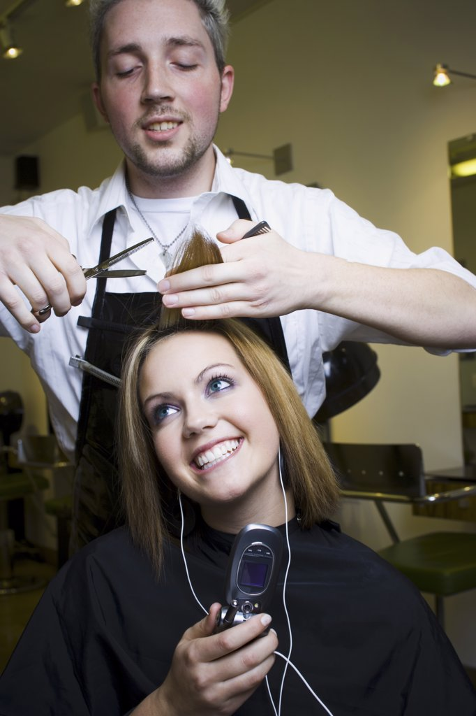 Young woman listening to music on cell phone at hairdresser's : Stock Photo