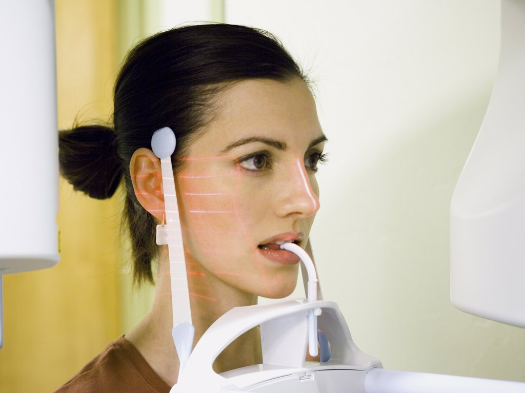 Stock Photo: 1660R-31689 Woman with dental laser x-ray machine in mouth