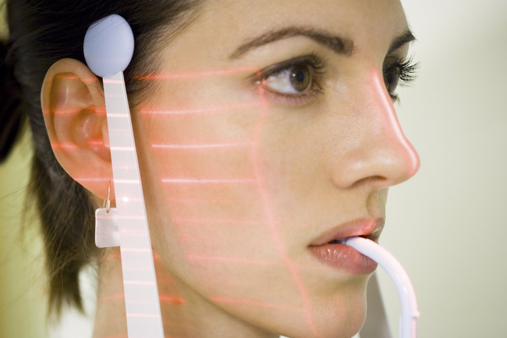 Stock Photo: 1660R-31691 Woman with dental laser x-ray machine in mouth