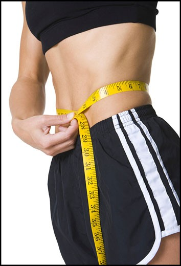 Young woman measuring her waist : Stock Photo