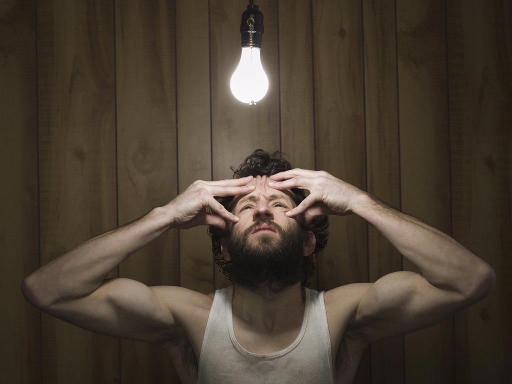 Stock Photo: 1660R-31787 Man reaching to light bulb gritting teeth