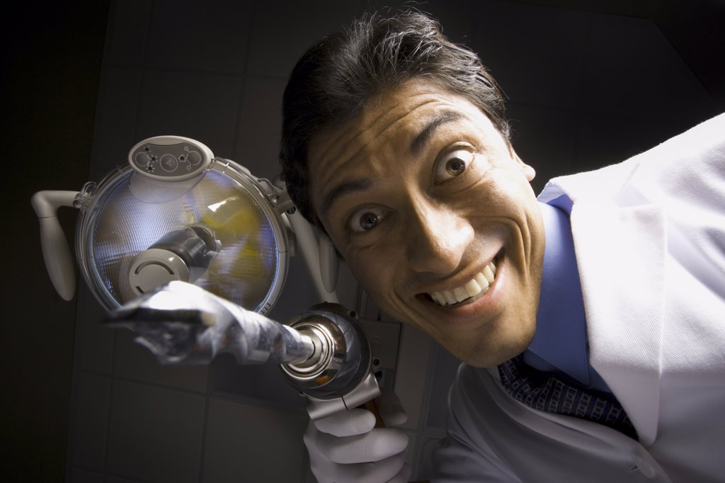 Dentist with drill dramatic angle : Stock Photo