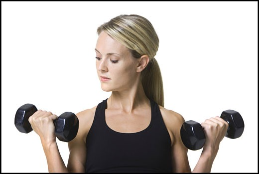 Stock Photo: 1660R-3183 Young woman working out with dumbbells