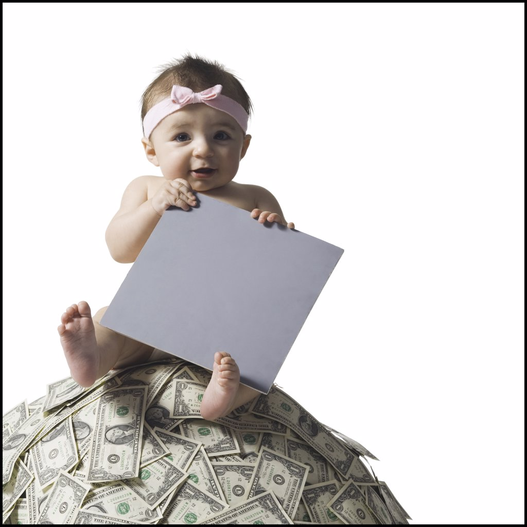 Baby girl sitting on pile of US currency with blank sign : Stock Photo
