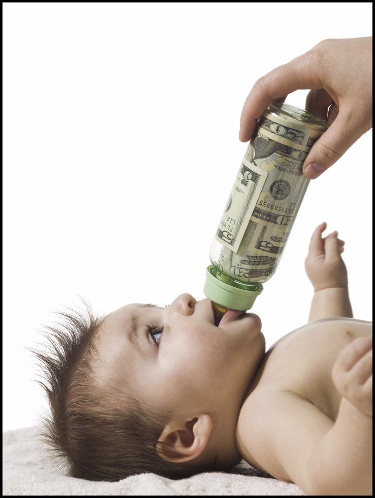 Stock Photo: 1660R-32395 Baby drinking from bottle with US currency in it