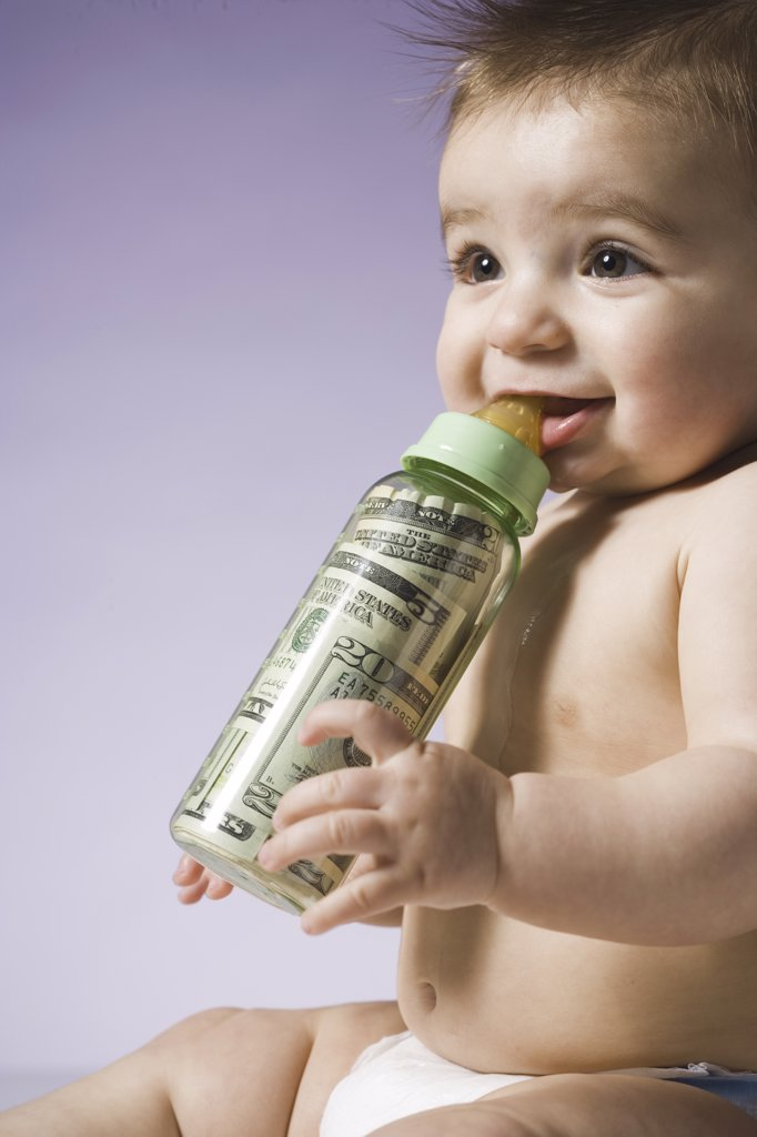 Stock Photo: 1660R-32404 Baby drinking from bottle with US currency in it
