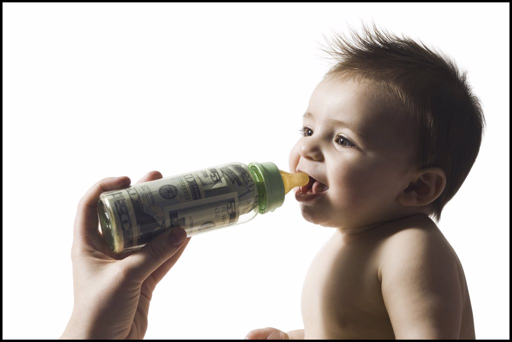 Baby drinking from bottle with US currency in it : Stock Photo
