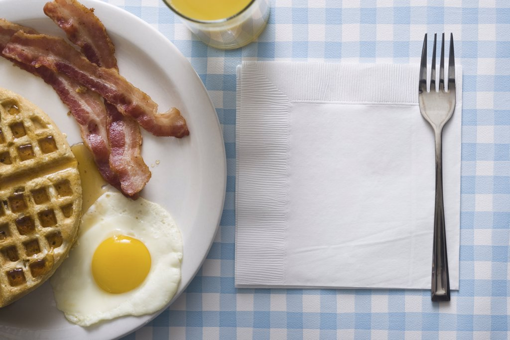 Bacon and eggs with waffle and orange juice with napkin and fork : Stock Photo