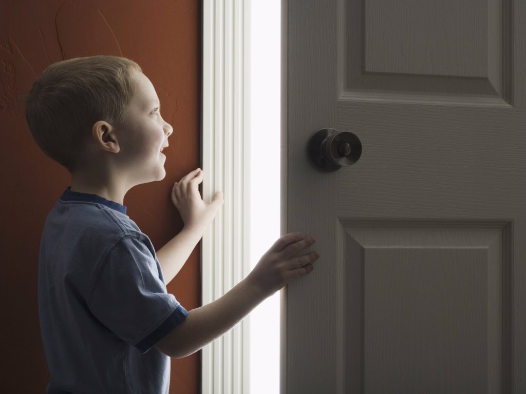 Young boy looking through doorway with mouth open : Stock Photo