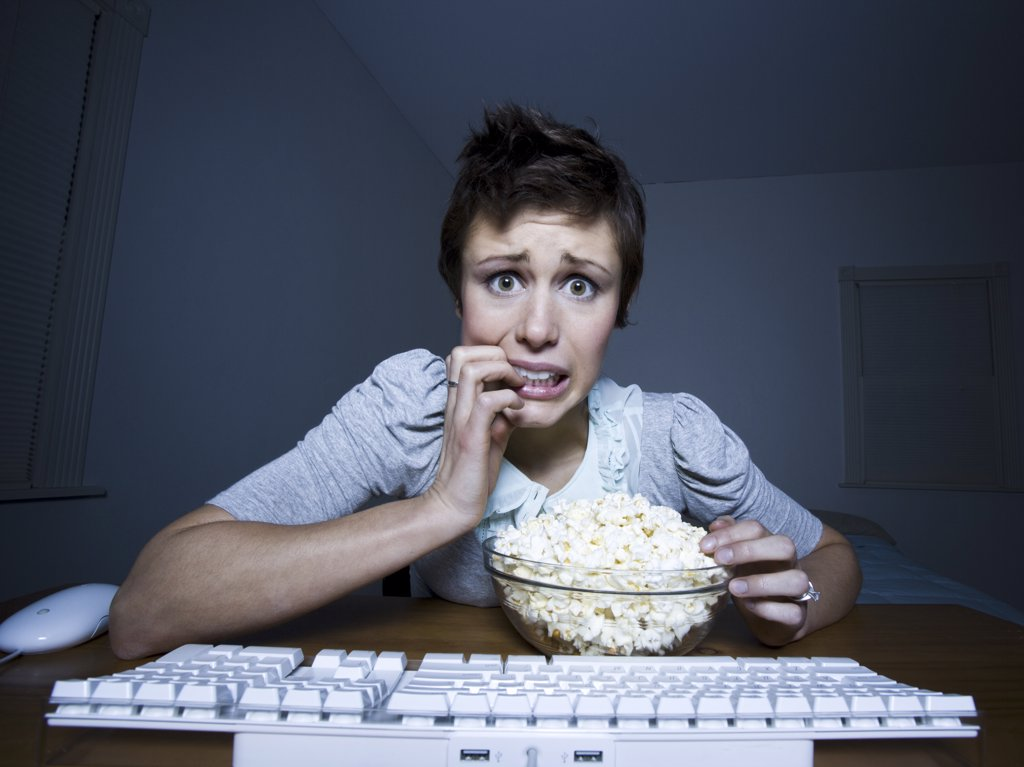 Stock Photo: 1660R-32972 Woman sitting at keyboard with bowl of popcorn