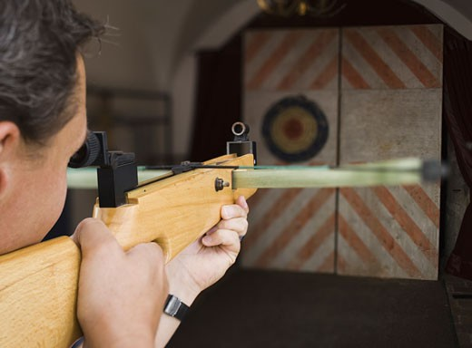 Close-up of a young man aiming at a target : Stock Photo