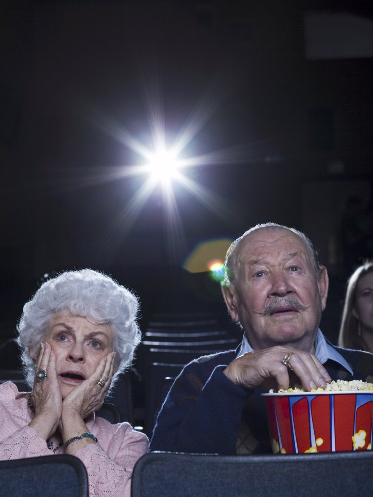 Man and woman watching film at movie theatre frightened : Stock Photo