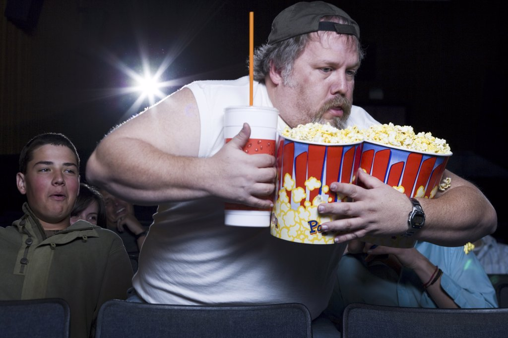 Stock Photo: 1660R-33513 Large man with buckets of popcorn and drink at movie theater