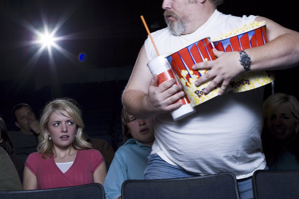 Large man with buckets of popcorn and drink at movie theater : Stock Photo