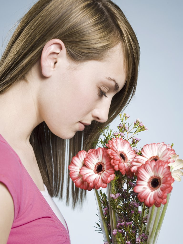 Profile of woman smelling flowers : Stock Photo