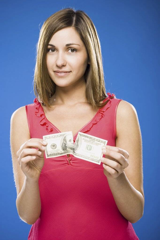 Stock Photo: 1660R-34071 Woman tearing American hundred dollar bill