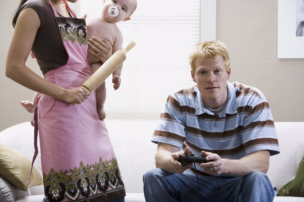 Man on sofa with video game controller and woman in apron with rolling pin holding baby : Stock Photo