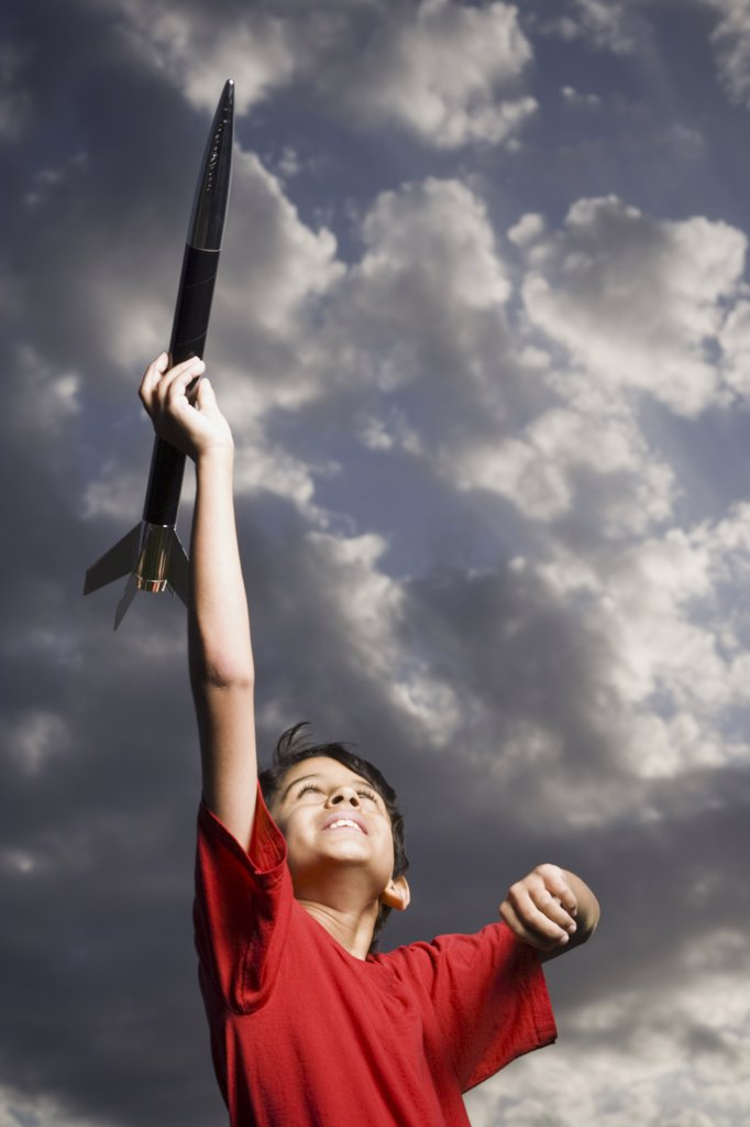 Boy playing with toy rocket outdoors on cloudy day low angle view : Stock Photo