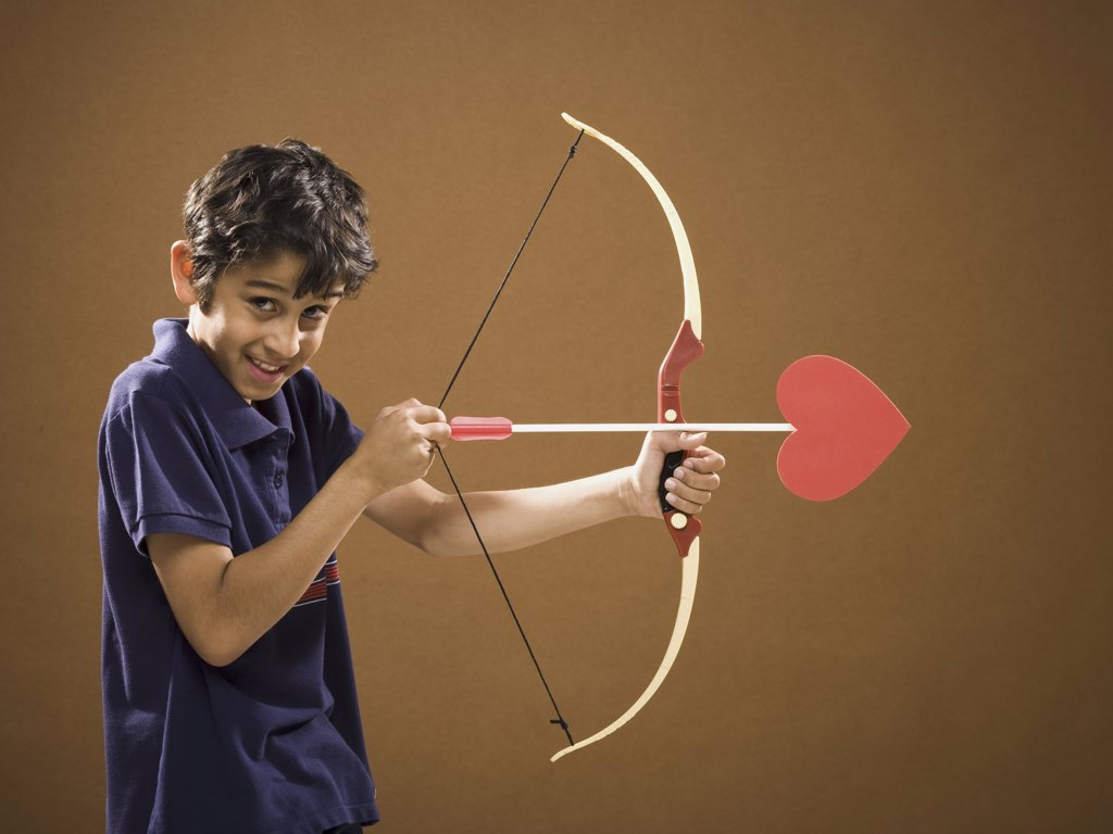 Boy with bow and arrow with heart on it : Stock Photo