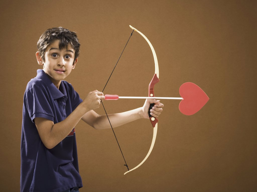 Stock Photo: 1660R-34462 Boy with bow and arrow with heart on it