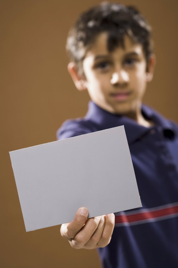 Boy holding blank card smiling : Stock Photo